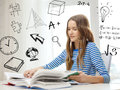 Smiling student girl reading books at home education and concept sitting table and Royalty Free Stock Photo