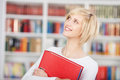 Smiling student holding binder in library front of book shelves Royalty Free Stock Photography