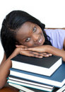 Smiling student leaning on a stack of books Royalty Free Stock Photos