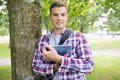 Smiling student leaning on tree holding his digital tablet Royalty Free Stock Photo