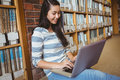 Smiling student sitting on the floor against wall in library using laptop Royalty Free Stock Photo
