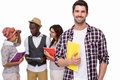 Smiling student standing with friends behind him Royalty Free Stock Photo
