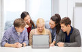 Smiling students looking at blank lapotop screen education technology advertisement and internet concept group of black laptop Royalty Free Stock Photos