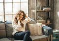 Smiling stylish woman sitting on divan and talking smartphone Royalty Free Stock Photo