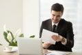 Smiling successful businessman holding document, reading good ne Royalty Free Stock Photo