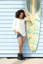 Smiling in summer full length portrait of a beautiful young woman standing outdoors next to surfboard Stock Photography