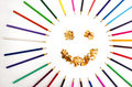 Smiling sun arranged from crayons and pencil sharpenings on white background Stock Photos