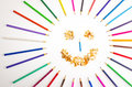 Smiling sun arranged from crayons and pencil sharpenings on white background Stock Images