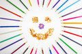 Smiling sun arranged from crayons and pencil sharpenings on white background Royalty Free Stock Images