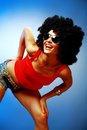 Smiling tanned woman sunglesses afro hair posing against blue background Royalty Free Stock Photography