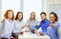 Smiling team with table pc and papers working business office gesture startup concep creative computers showing thumbs up in Royalty Free Stock Image