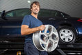Smiling technician holding alloy at repair shop low angle portrait of metallic auto Royalty Free Stock Photo