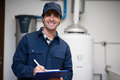 Smiling technician servicing an hot-water heater Royalty Free Stock Photo