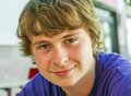 Smiling teen boy with blonde hair long Royalty Free Stock Photos