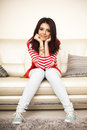 Smiling teen girl in colorful cloths sitting on the sofa and relaxing Royalty Free Stock Photo