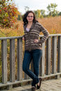 Smiling teen with sweater and jeans pretty teenage girl poses in a brown blue Stock Images