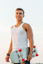 Smiling teenage boy with skateboard outdoors Royalty Free Stock Photo