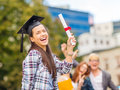 Smiling teenage girl in corner cap with diploma education campus and concept and classmates on the back Royalty Free Stock Photography