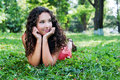 Smiling teenage girl with curly hair lying on a green grass portrait of outdoor Royalty Free Stock Image