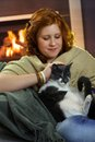 Smiling teenage girl fondling cat at home sitting fireplace and affectionate Royalty Free Stock Photo