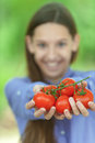 Smiling teenage girl holding red tomatoes against green of summer park Royalty Free Stock Image