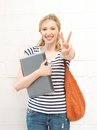 Smiling teenage girl with laptop picture of showing victory sign Stock Photo