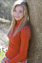 Smiling teenage girl leaning against tree Royalty Free Stock Photo