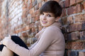 Smiling teenage girl leaning on the brick wall Royalty Free Stock Photo