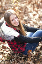 Smiling teenage girl with long brown hair and red plaid coat sitting in leaves in the fall. Royalty Free Stock Photo