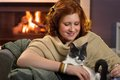 Smiling teenage girl loving her cat at home happy sitting fireplace caressing Royalty Free Stock Photos