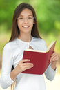 Smiling teenage girl reading red book against green of summer park Royalty Free Stock Photography
