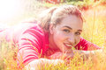Smiling teenage girl resting in the grass, psychedelic colorful effects