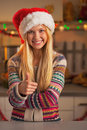 Smiling teenage girl in santa hat showing thumbs up in kitchen christmas decorated Royalty Free Stock Photo