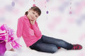Smiling teenage girl sitting in pink decoration Stock Photography