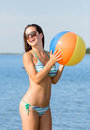 Smiling teenage girl sunglasses with ball on beach Royalty Free Stock Photo