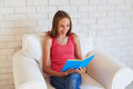 Smiling teenage girl in white armchair with a book against white Royalty Free Stock Photo