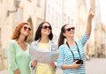 Smiling teenage girls with map and camera Royalty Free Stock Photo