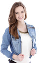 Smiling teenage woman in a denim jacket trendy looking at the camera upper body studio portrait on white Stock Images