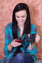 Smiling Teenager Drinking Coffee and Texting Royalty Free Stock Photo