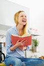Smiling teenager girl reading book in kitchen modern Stock Photography