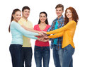 Smiling teenagers with hands on top of each other friendship youth and people concept group Royalty Free Stock Photo