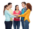 Smiling teenagers with hands on top of each other friendship youth and people concept group Royalty Free Stock Images