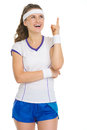 Smiling tennis player pointing up on copy space Royalty Free Stock Photo