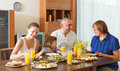 Smiling three generations family posing together over healthy table at home interior Stock Images