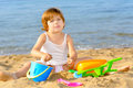 Smiling toddler girl playing her toys beach Royalty Free Stock Image