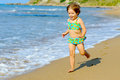 Smiling toddler girl running beach Royalty Free Stock Photos