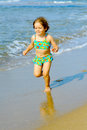 Smiling toddler girl running beach Stock Photo