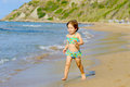 Smiling toddler girl running beach Stock Images
