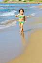 Smiling toddler girl running beach Stock Image
