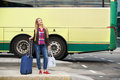 Smiling travel woman standing at bus terminal with bags Royalty Free Stock Photo